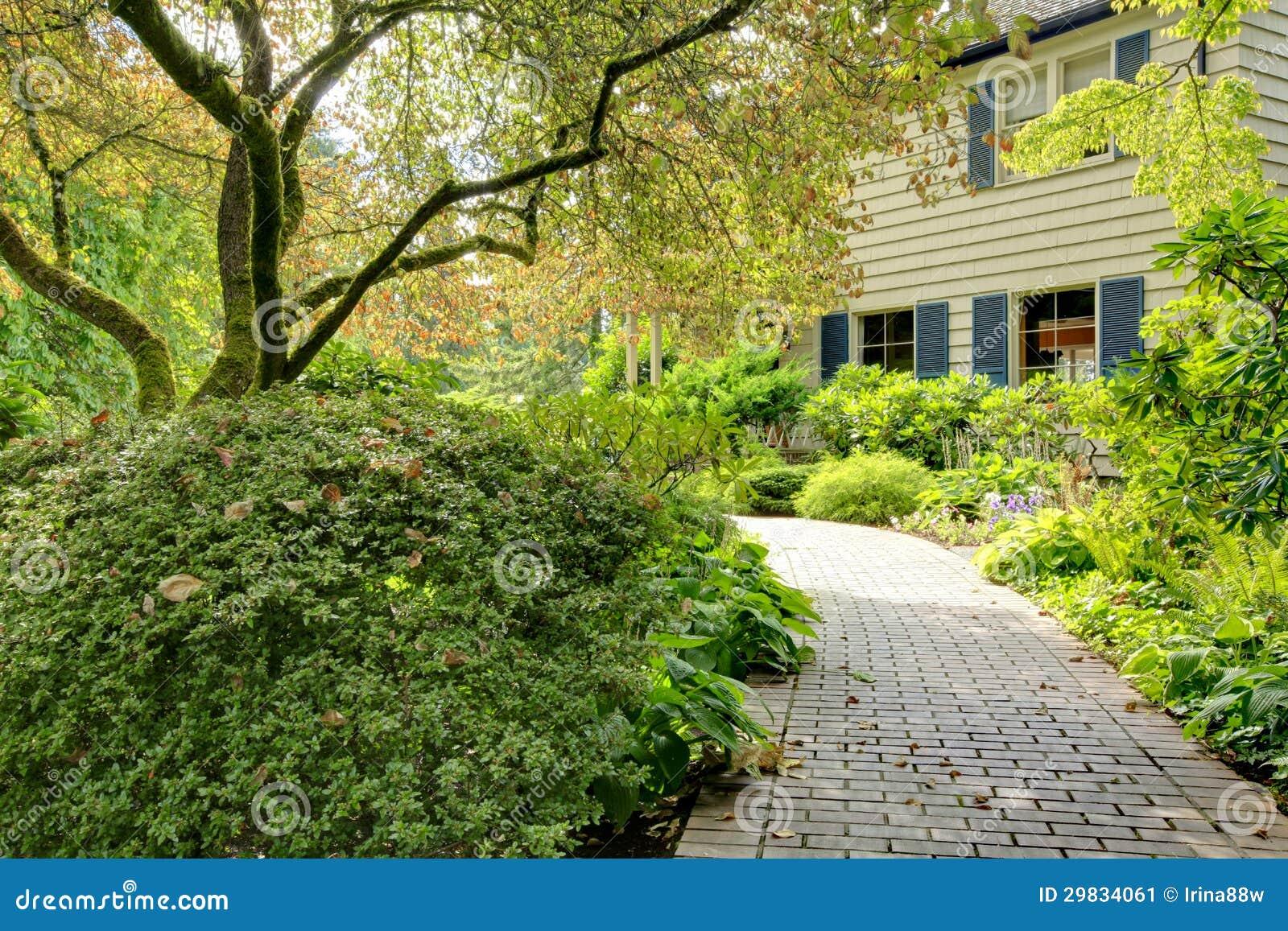 Grande casa marrom exterior com jardim do verão.
