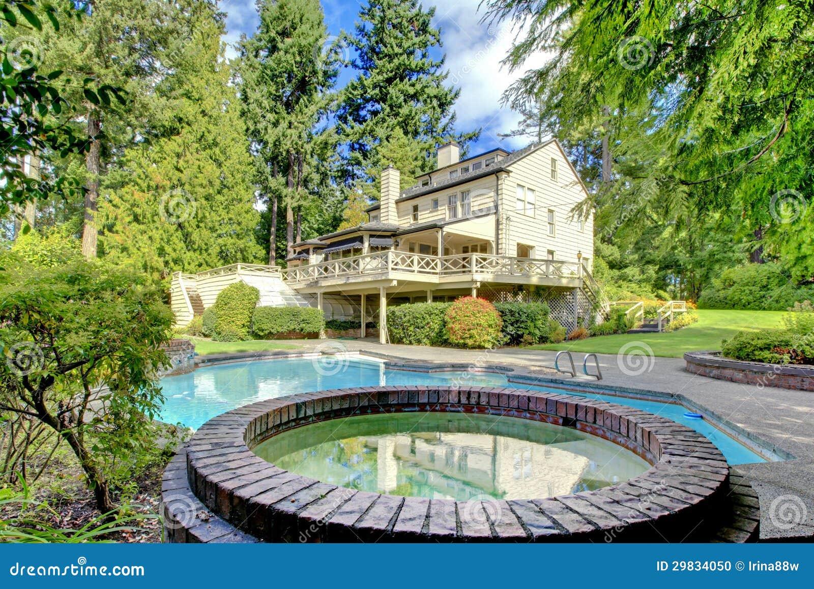 Grande casa marrom exterior com o jardim do verão com associação.