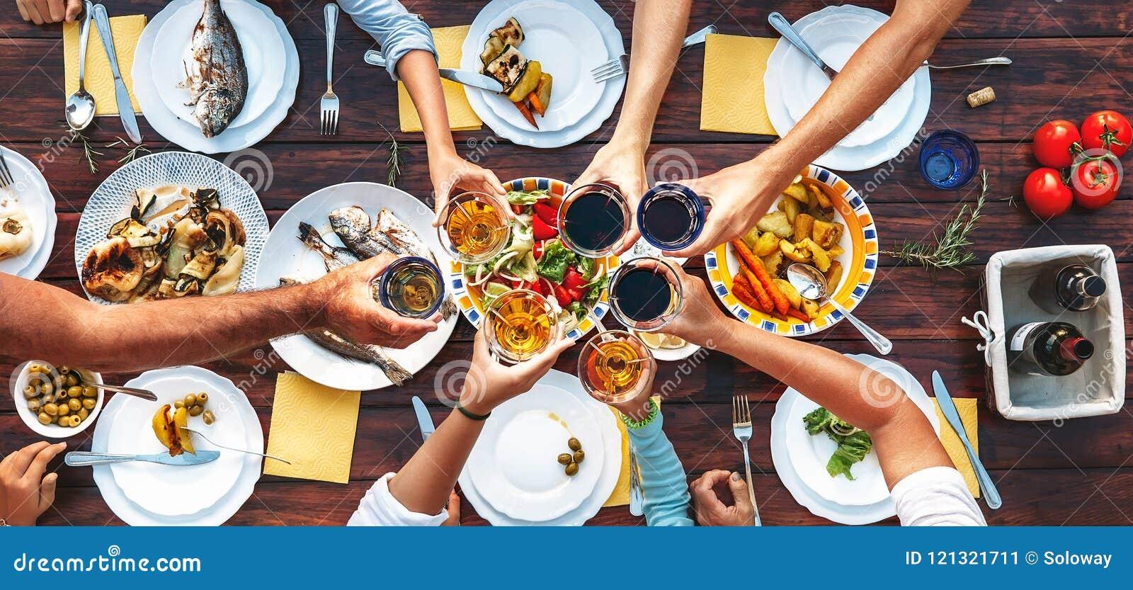 Grande cena della famiglia Vista superiore verticale sulla tavola e sulle mani servite w
