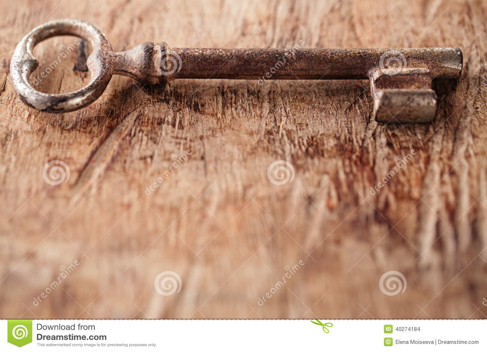 Grande chave oxidada do metal do vintage no fundo de madeira velho