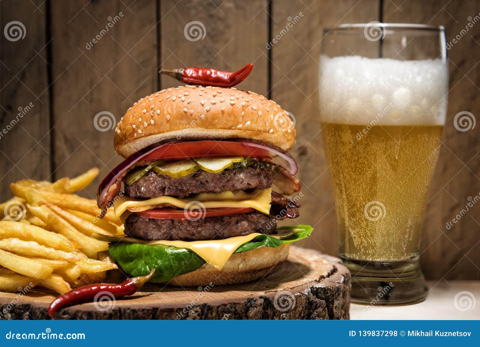 Grande cheeseburger con peperoncino, le patate fritte e un vetro di birra su fondo di legno