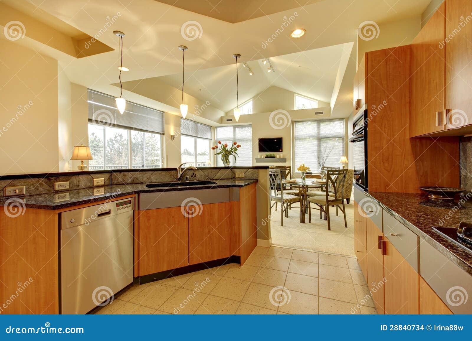 Grande cozinha de madeira moderna com sala de visitas e teto alto.
