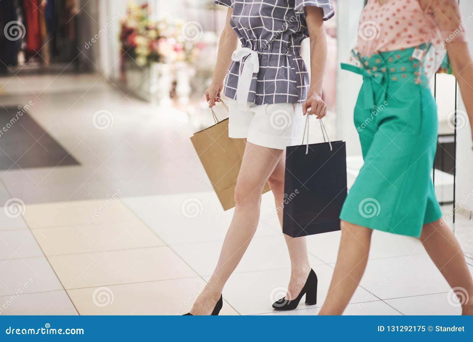 Grande dia para comprar Duas mulheres bonitas com os sacos de compras que olham se com sorriso ao andar no