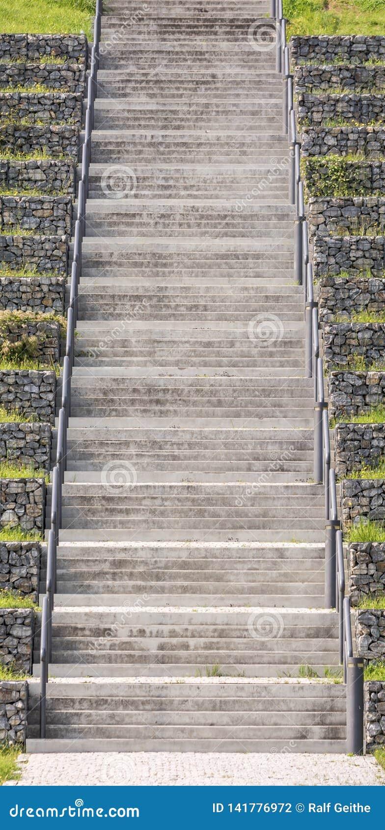 Grande escadaria concreta com trilhos como um símbolo da escada da carreira