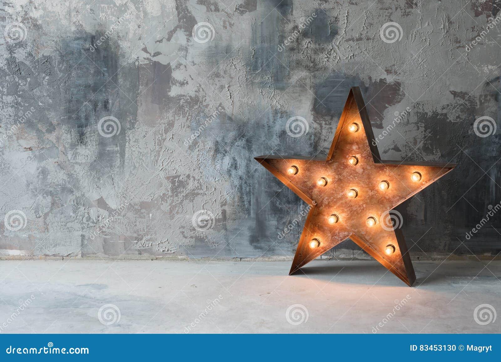 Grande estrela retro decorativa com lotes de luzes ardentes no fundo do concreto do grunge Decoração bonita, projeto moderno