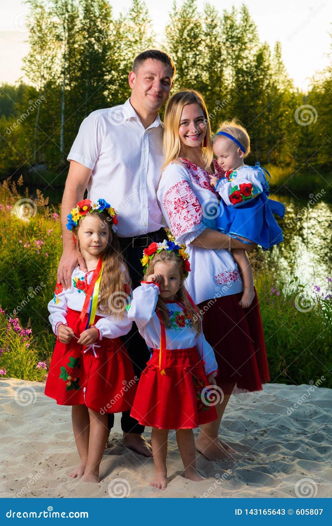 A grande família em trajes ucranianos étnicos senta-se no prado, o conceito de uma grande família