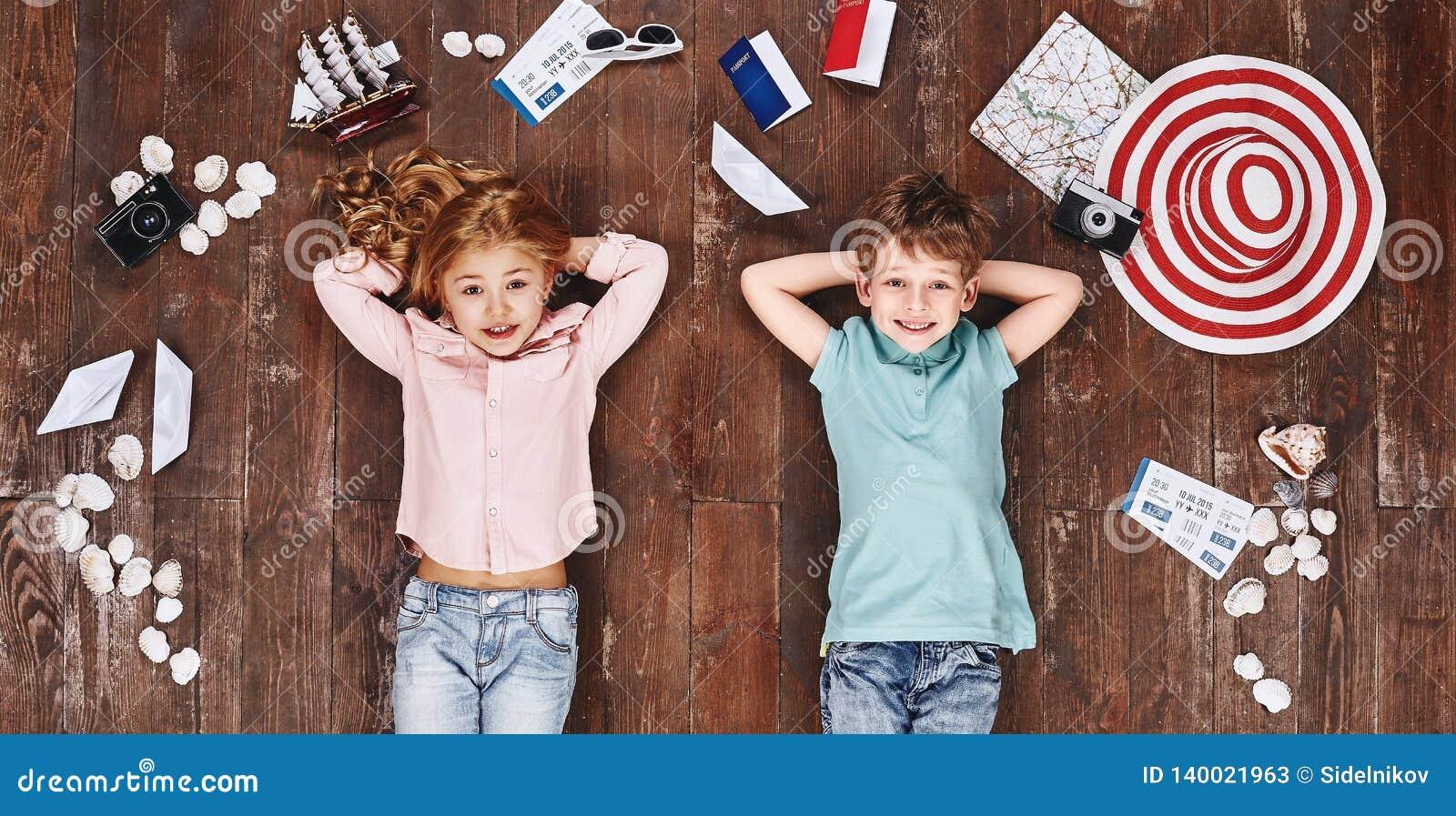 Grande ideal Crianças que encontram-se perto dos artigos do curso, olhando a câmera e o sorriso