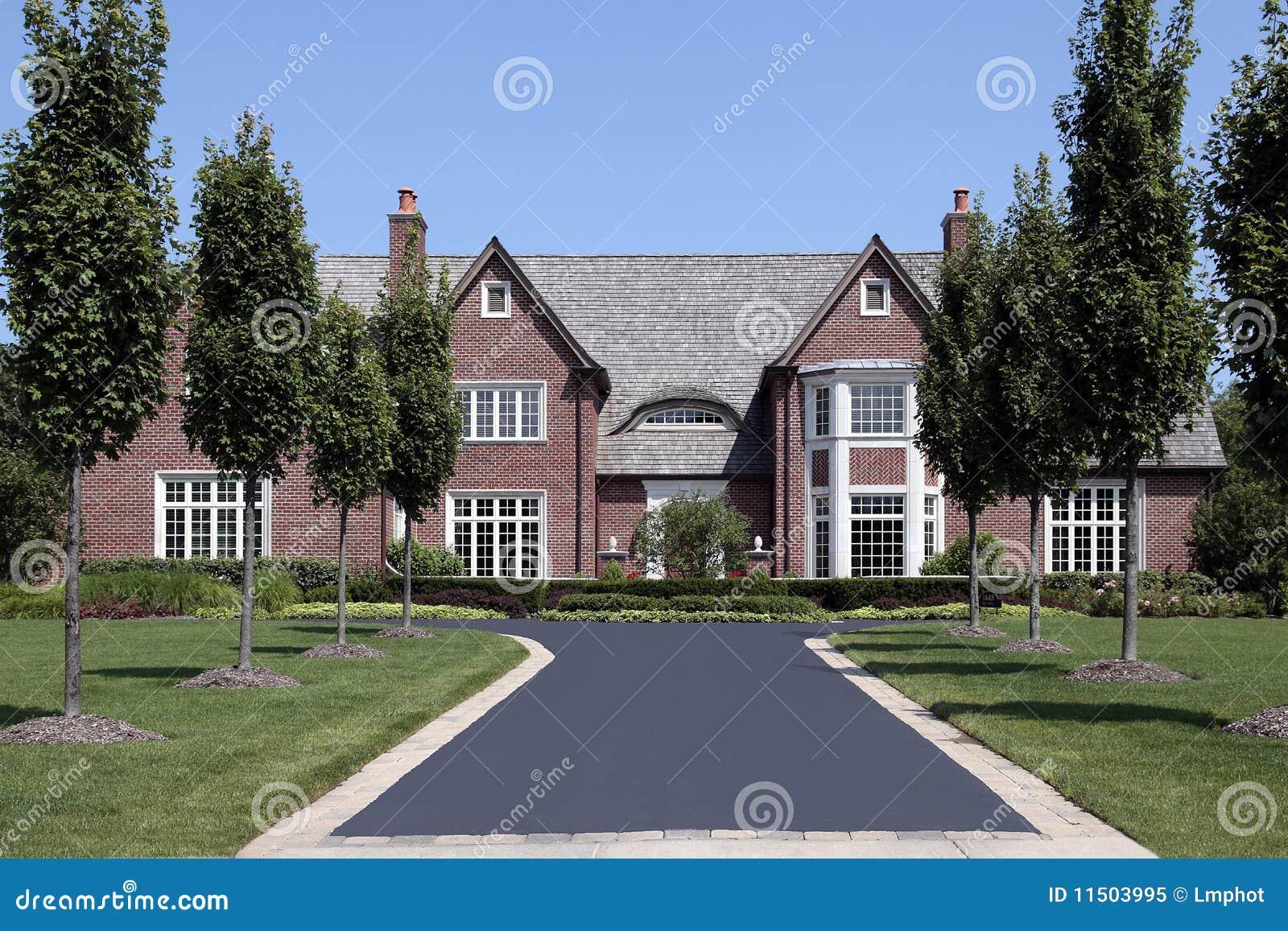 Grande maison de brique avec la ligne des arbres image for Brique exterieur maison