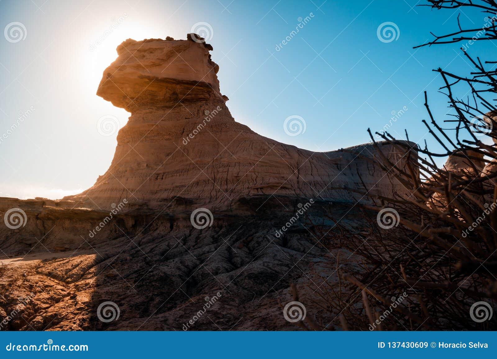 Grande montanha árida com o sol atrás