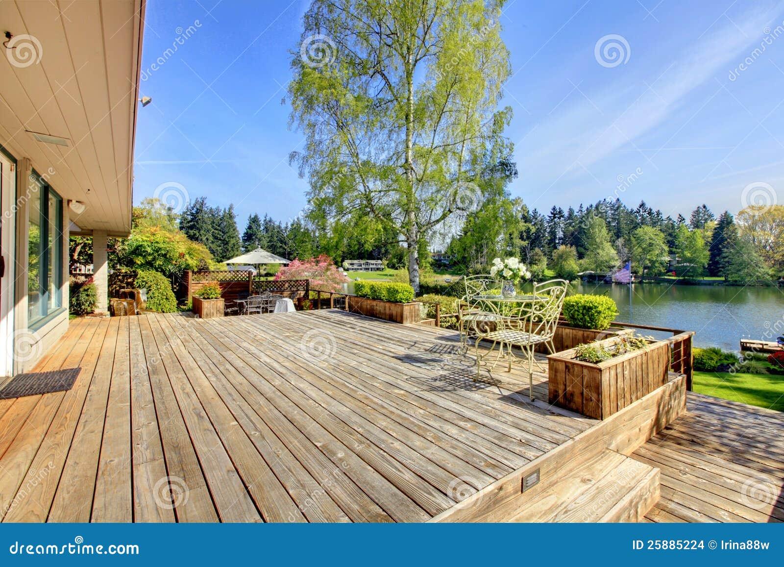 A grande plataforma de madeira com lago e a mola ajardinam.