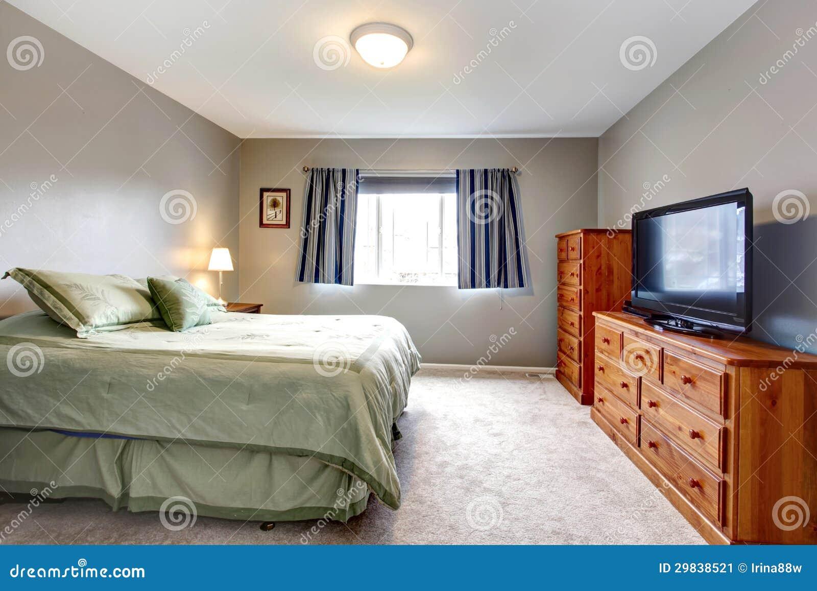 Grande quarto cinzento com armário, tevê e as cortinas azuis.