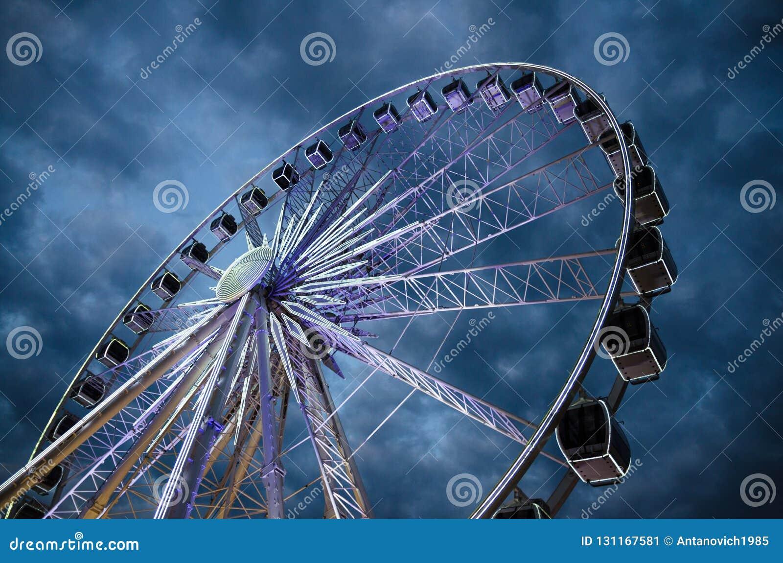 Grande roue de ferris lumineuse devant le ciel dramatique bleu-foncé