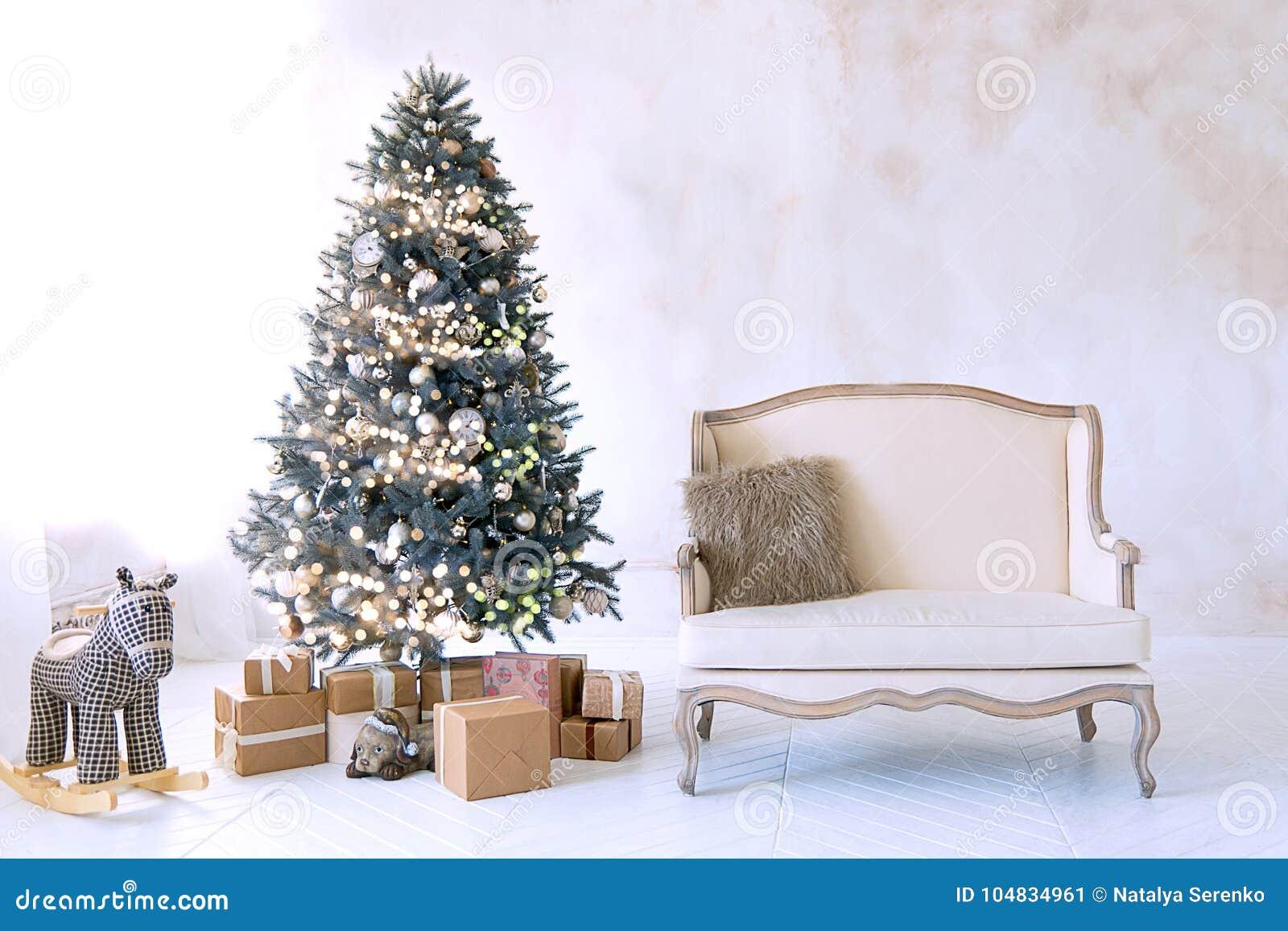 Grande sala de visitas branca com um sofá do vintage e uma grande árvore de Natal