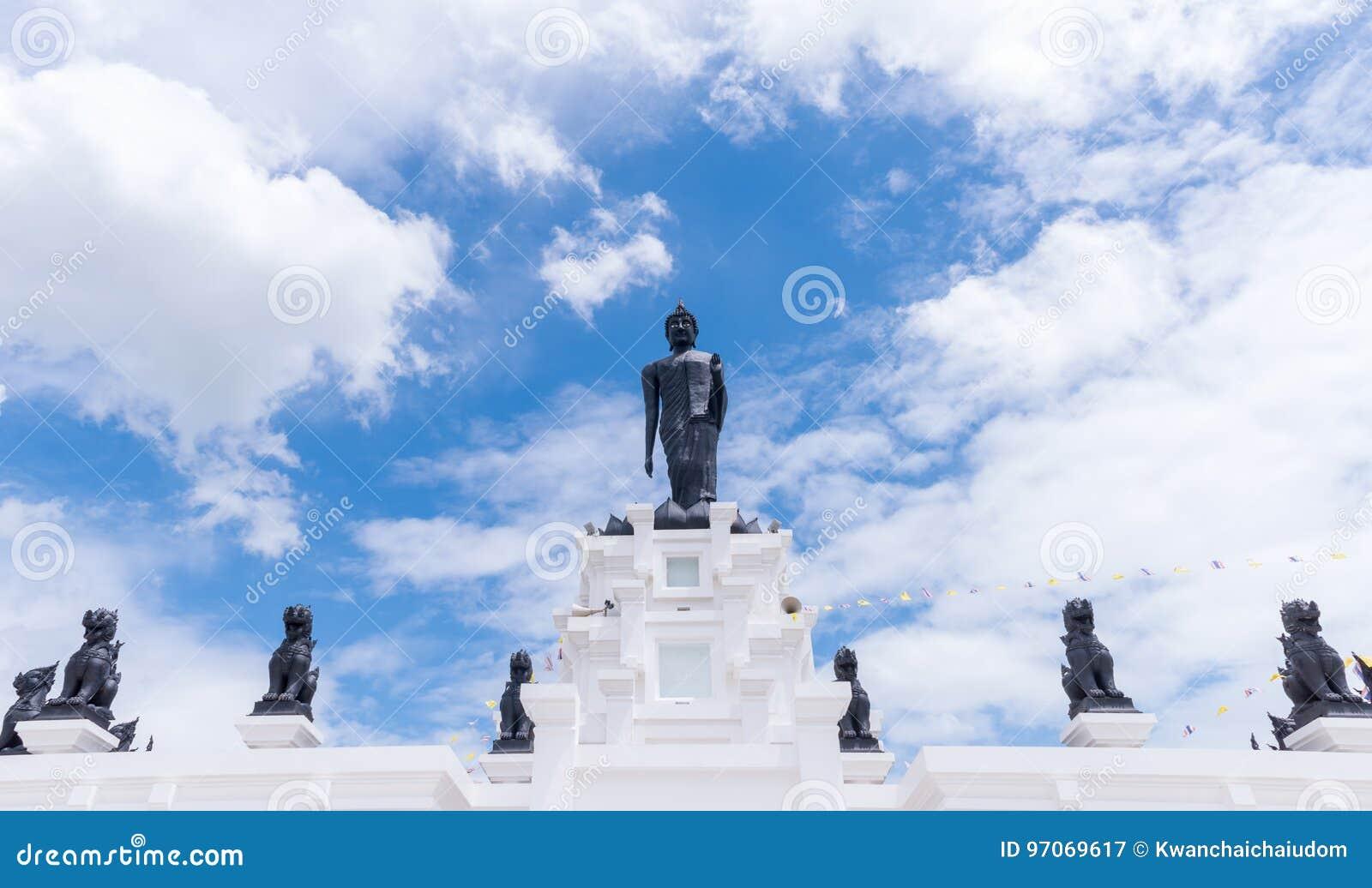 Grande statue noire de Bouddha avec le ciel nuageux et bleu blanc