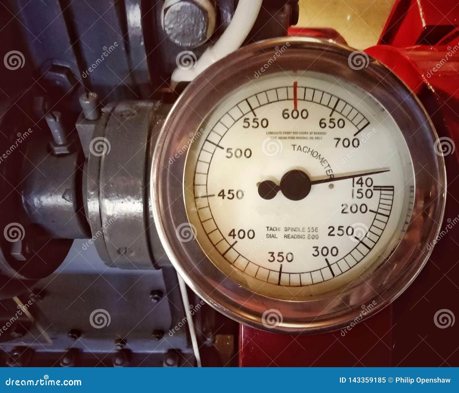 Grande tacômetro velho do metal com um calibre redondo com o seletor marcado nos números montados em um grande motor