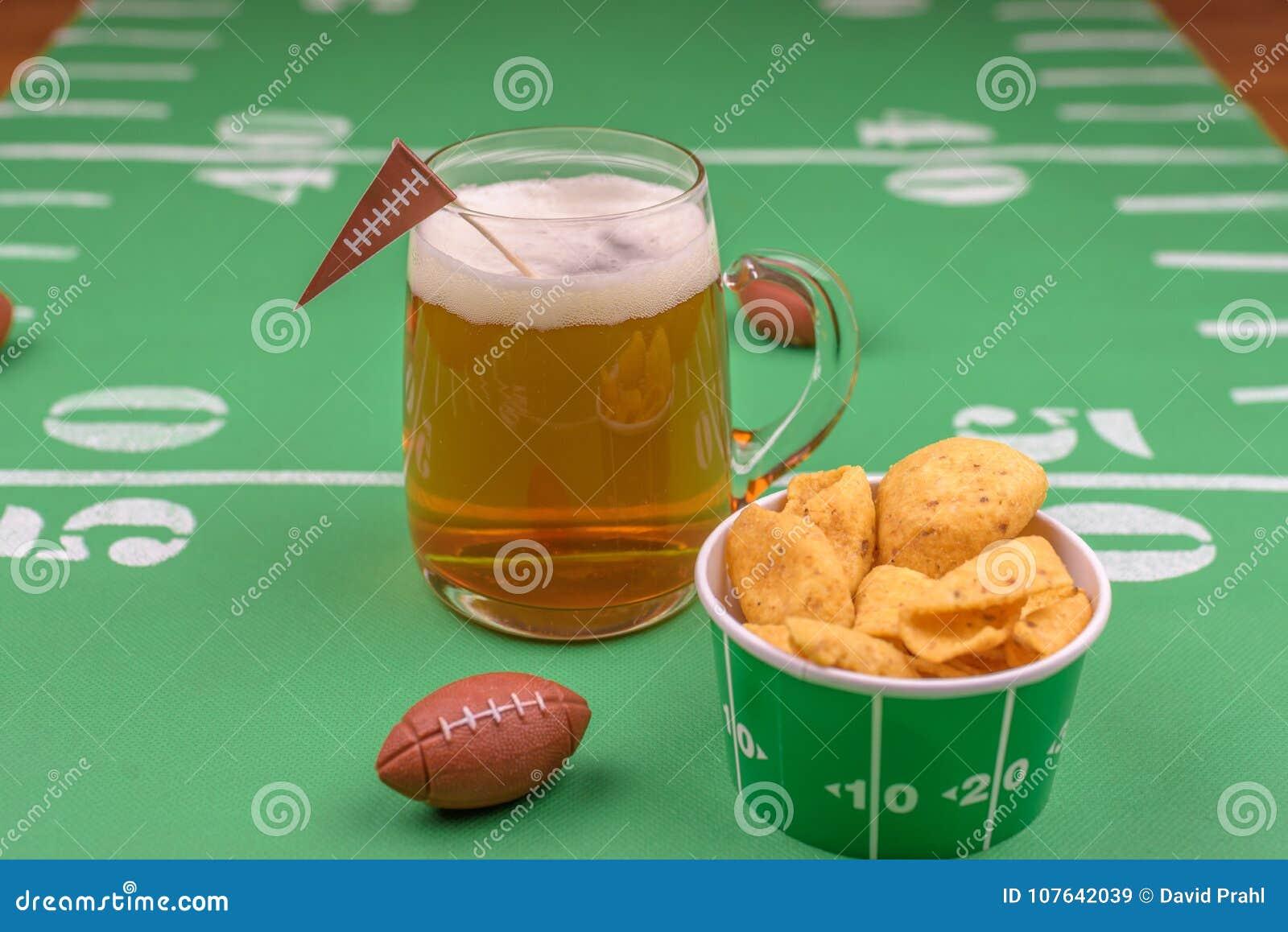 Grande tasse en verre de bière froide sur la table avec le décor de partie de superbowl