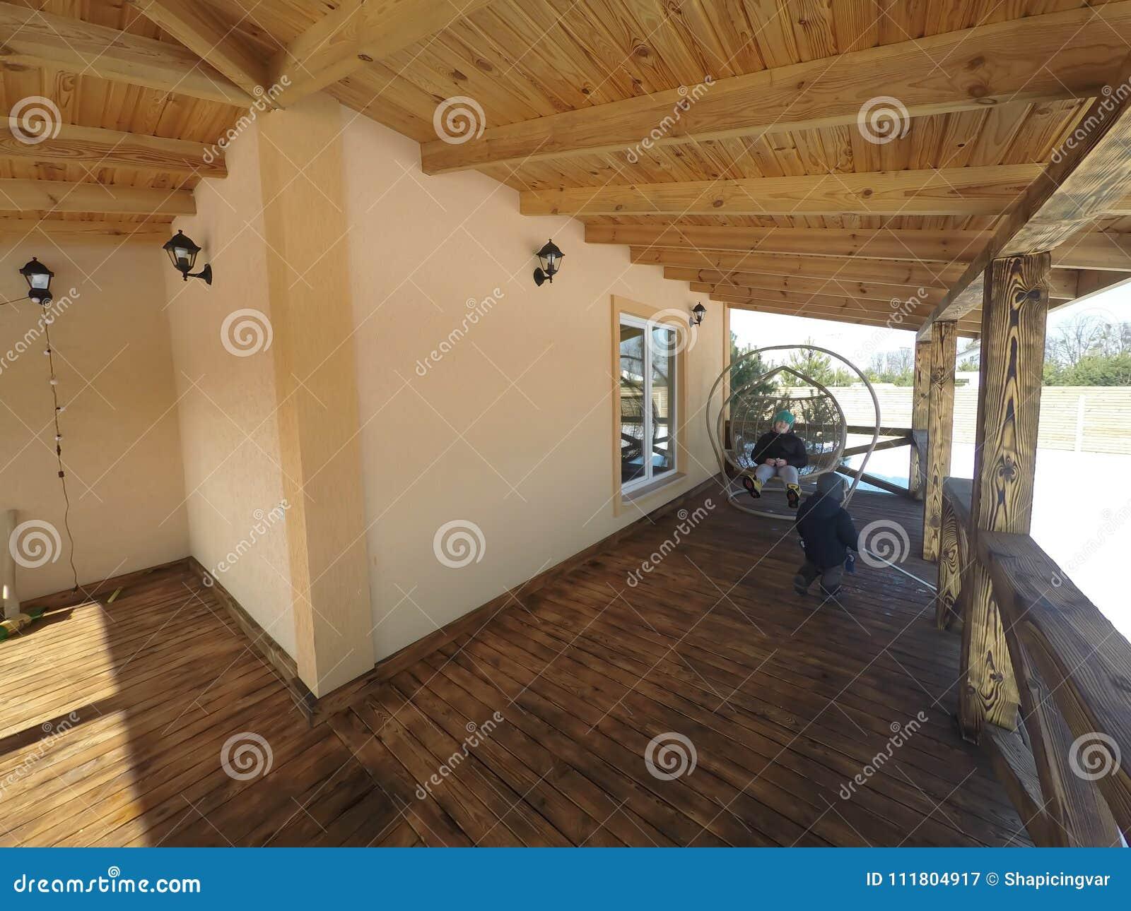 Grande terrasse en bois dans le chalet traditionnel avec les fenêtres et la forêt panoramiques de pin autour