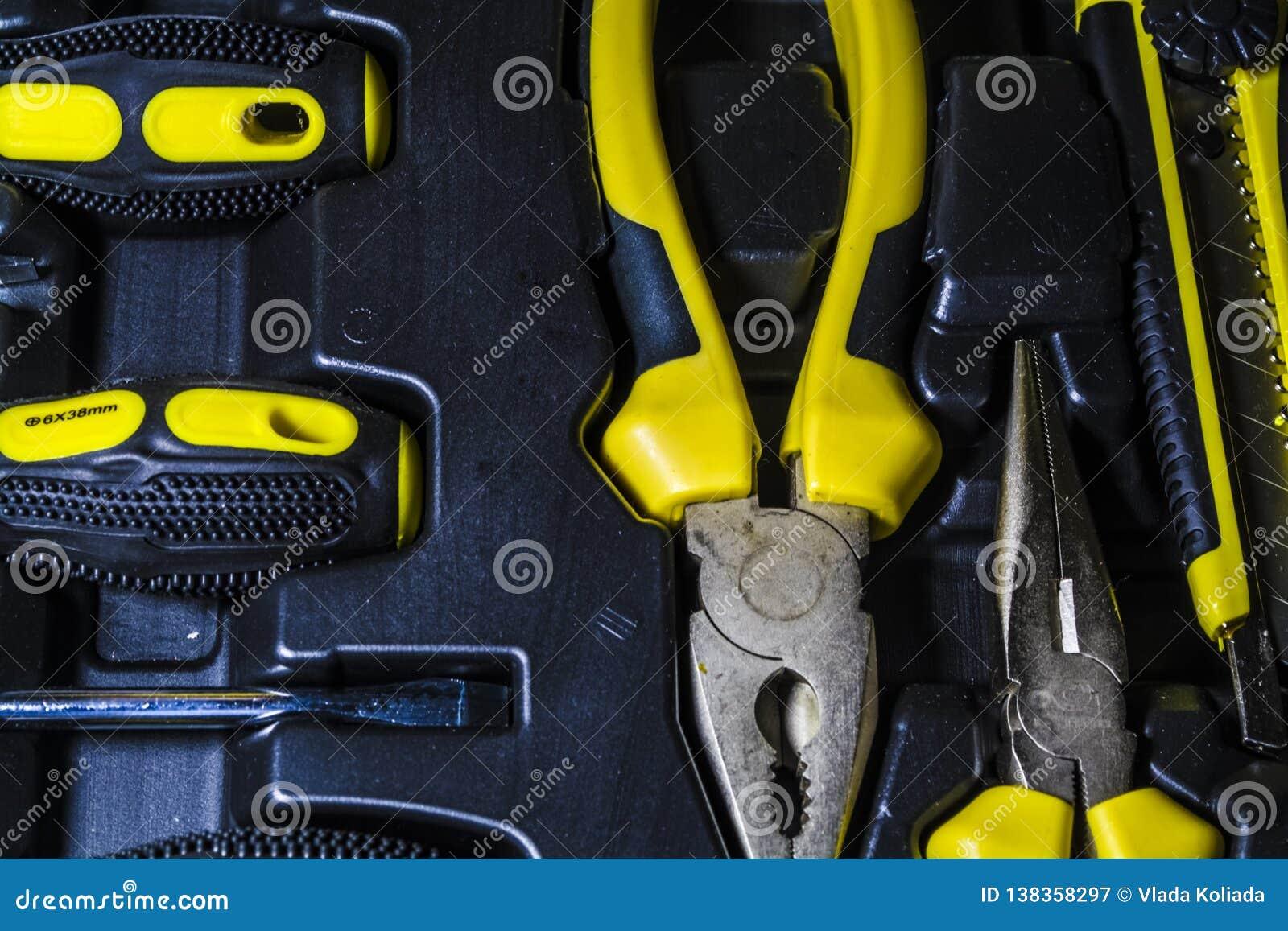 Grande trousse à outils de couleurs noires et jaunes pour la maison dans une boîte Pinces, tournevis, couteau de papeterie et pin