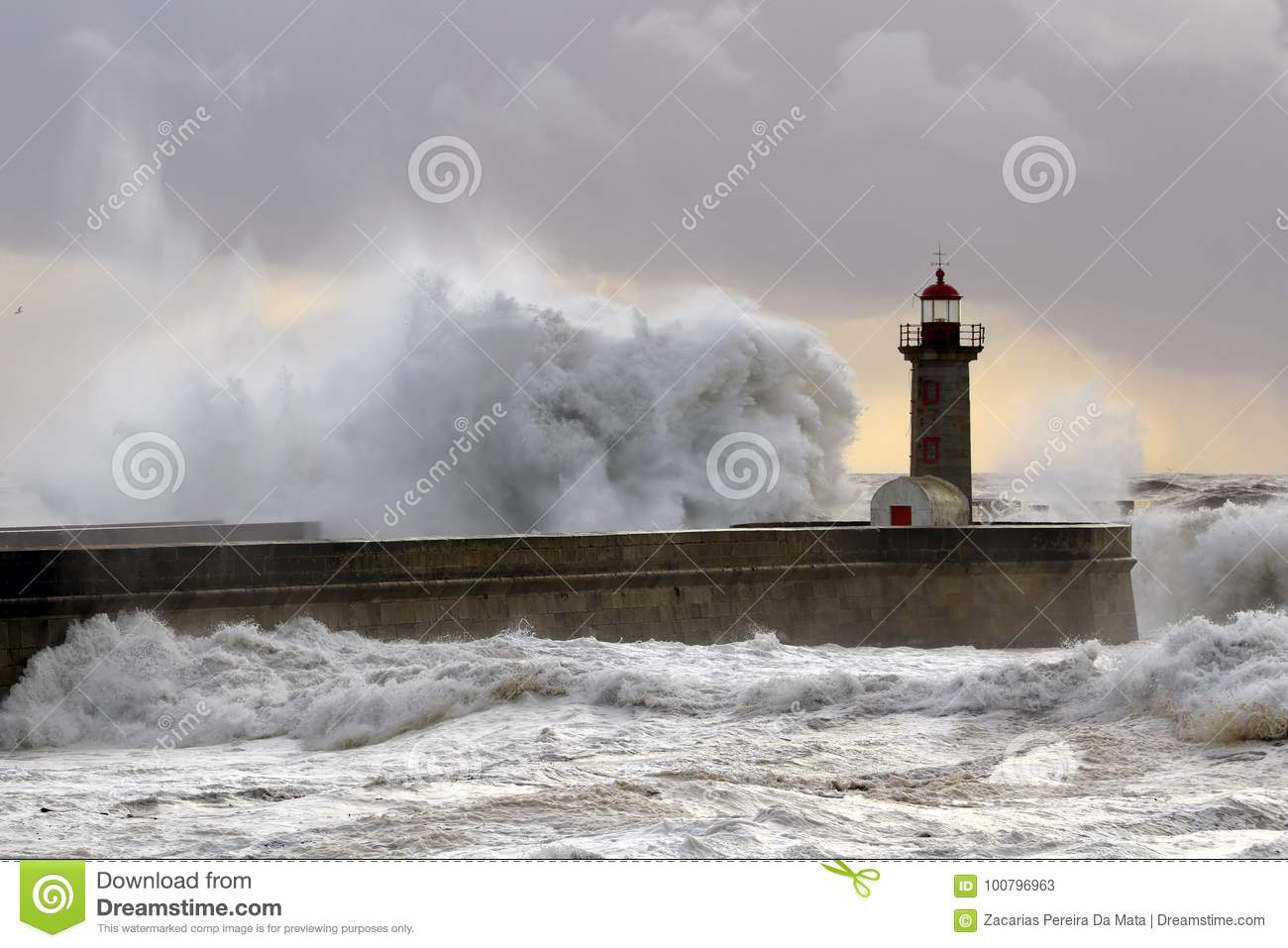 Grande vague contre le phare au coucher du soleil