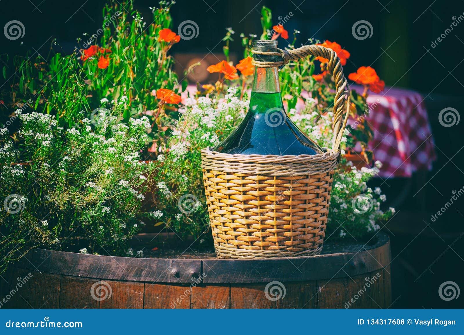 Grandes bouteilles de vin de vintage dans le panier en osier sur un baril