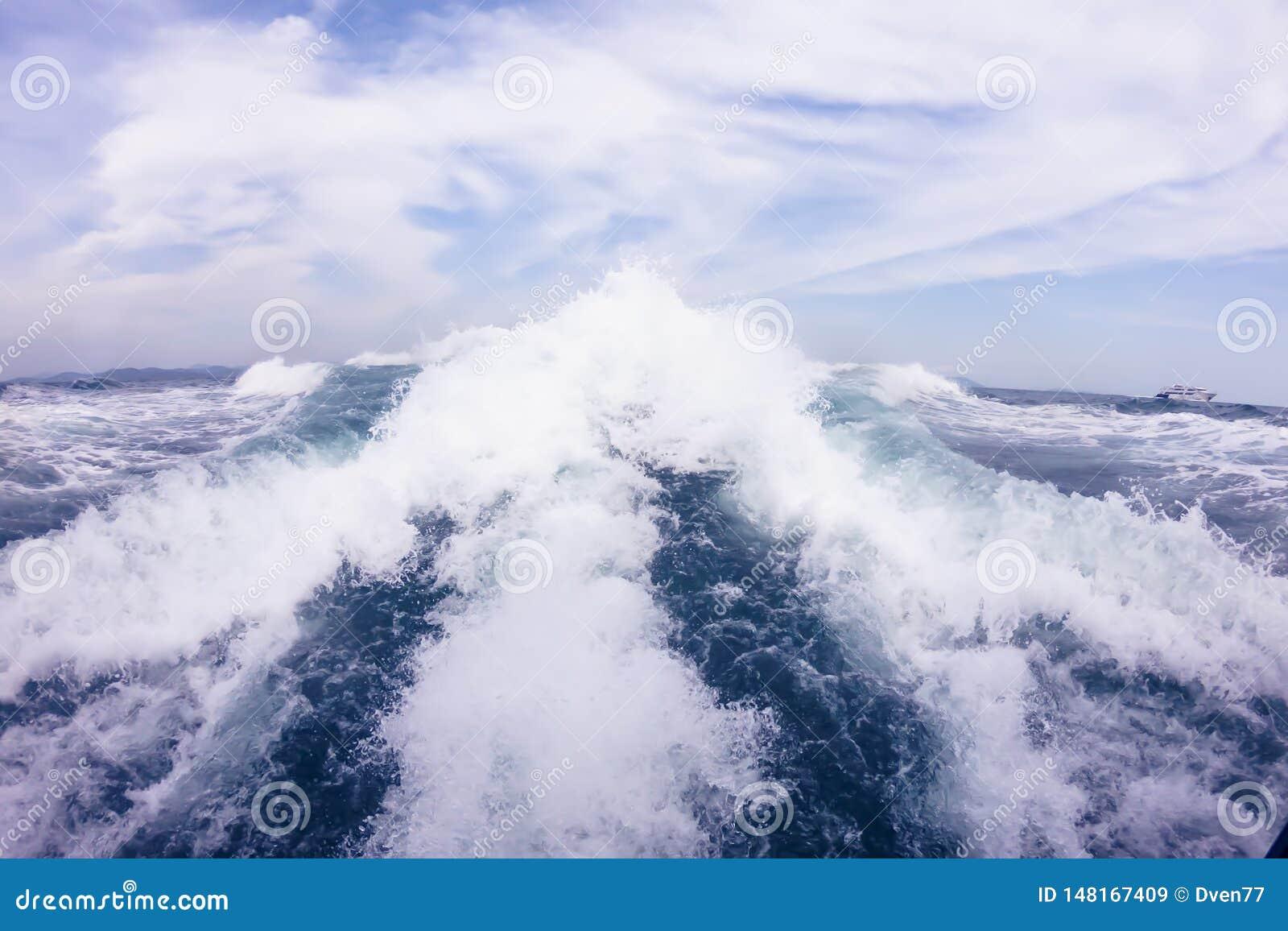 Grandes vagues du moteur derrière le hors-bord sur les hautes mers Ciel bleu avec les nuages blancs