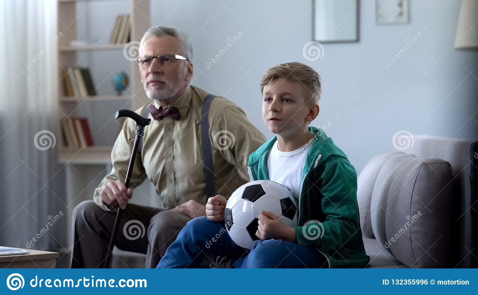 Grandfather and boy watching football at home, worrying about match result