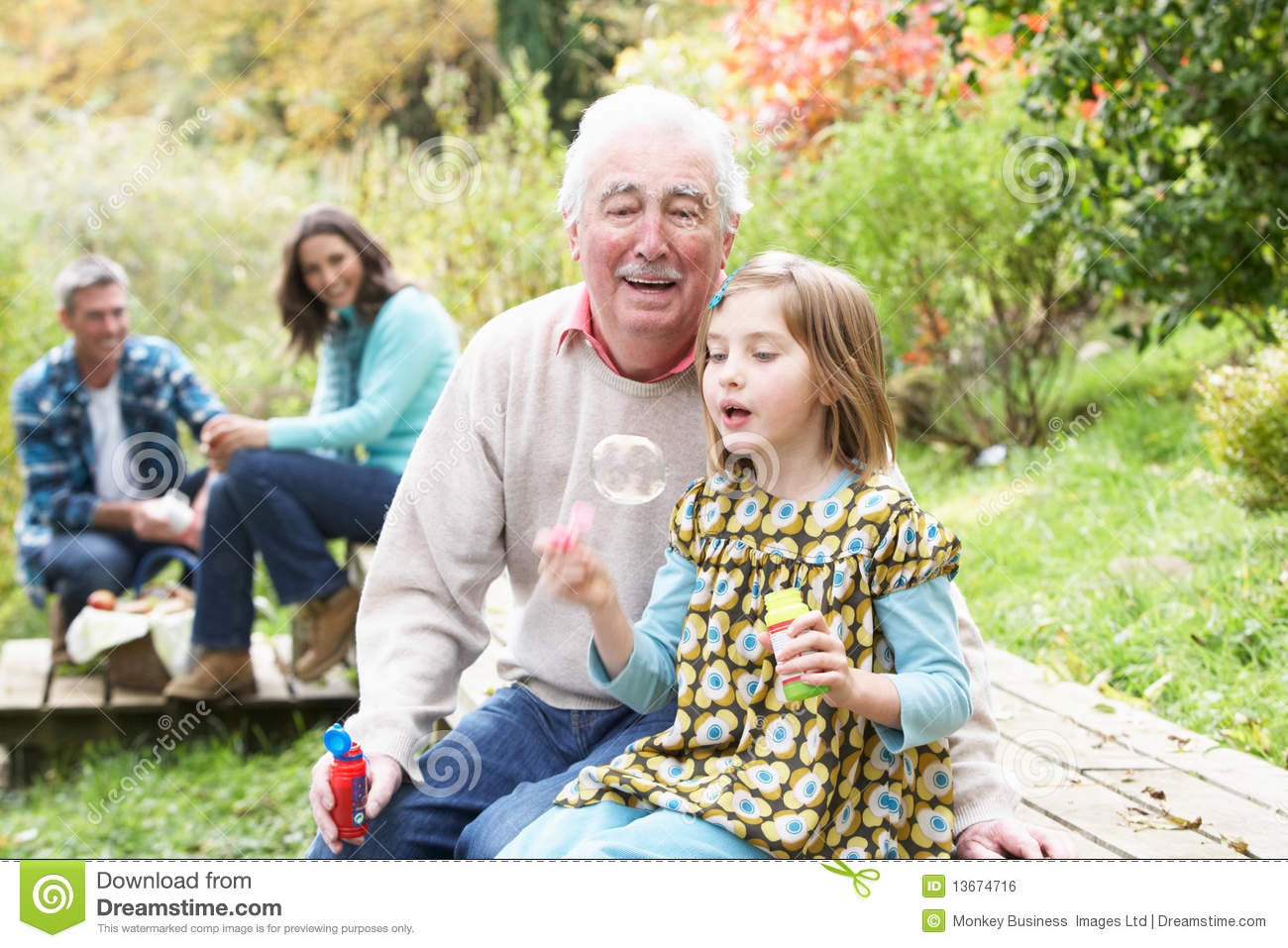 Grandpa and his granddaughter walking in a park. by