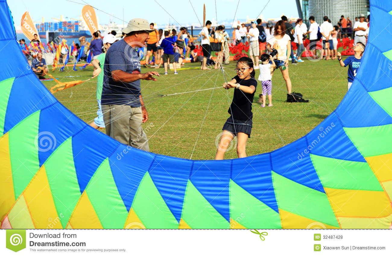 Grandfather is teaching granddaughter flying kite