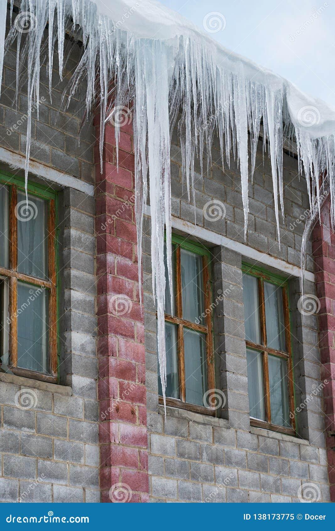 Grandi ghiaccioli che appendono sul tetto