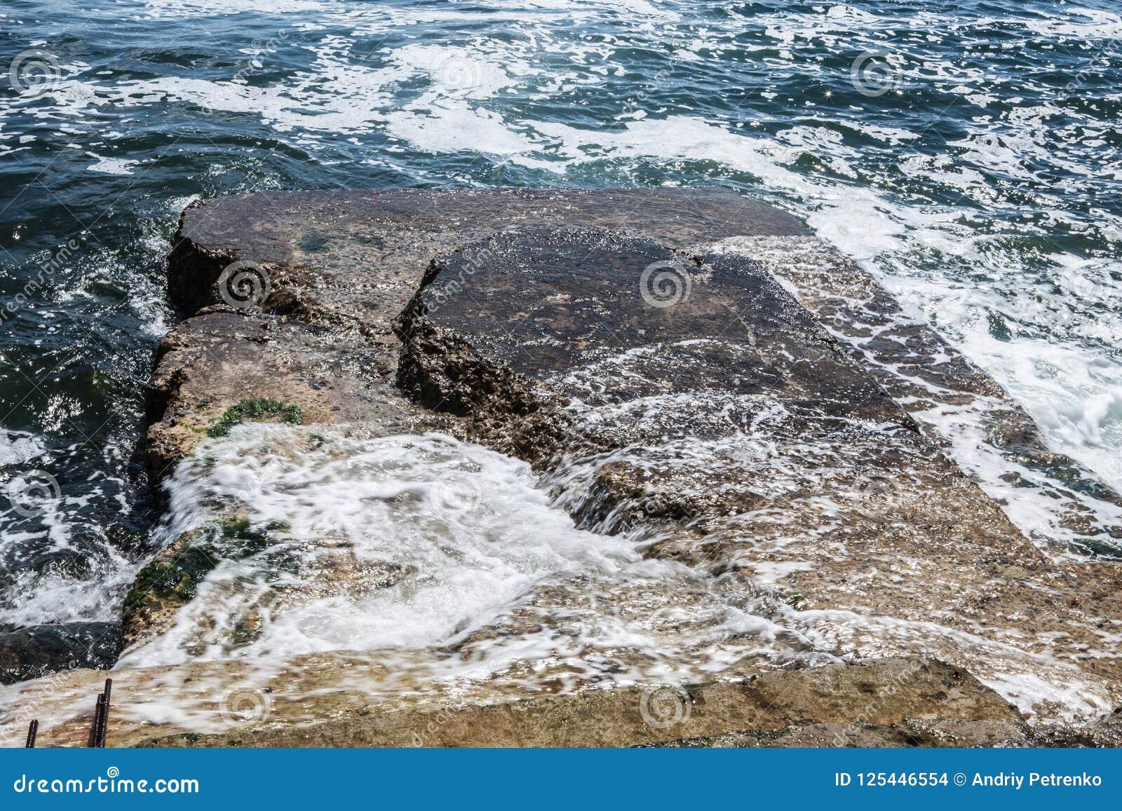 Grandi onde sulla costa rocciosa e sul mare blu
