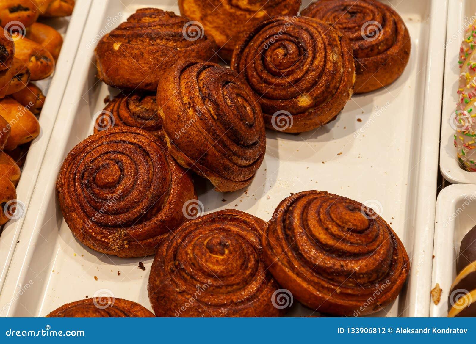 Grandi panini marroni appetitosi con cannella sotto forma di spirali c