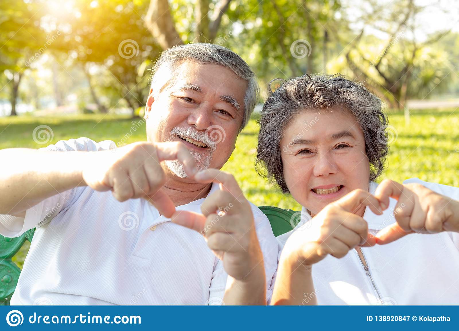 Grandma and grandpa or grandparents make symbol of love by using hands and fingers for making hearts. Lovely older couple or