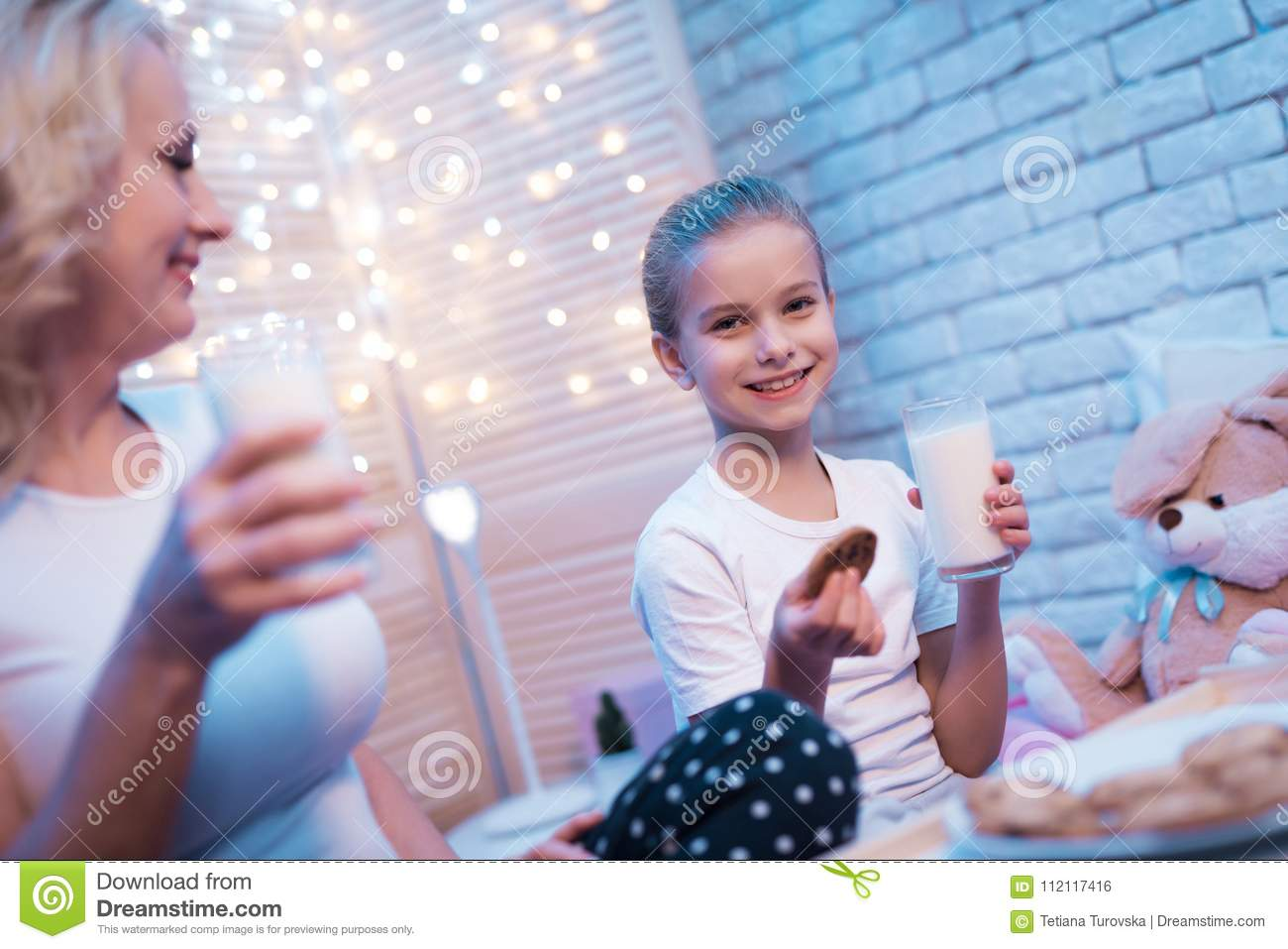 Grandmother and granddaughter are enjoying milk and cookies at night at home.