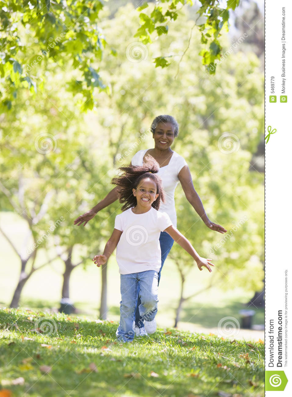 Grandmother and granddaughter running in park and