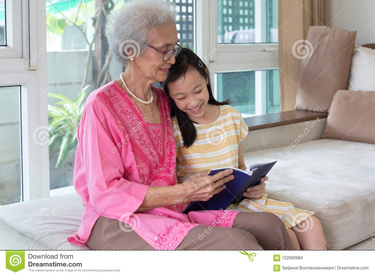 Grandmother and granddaughter sitting on sofa and reading book h