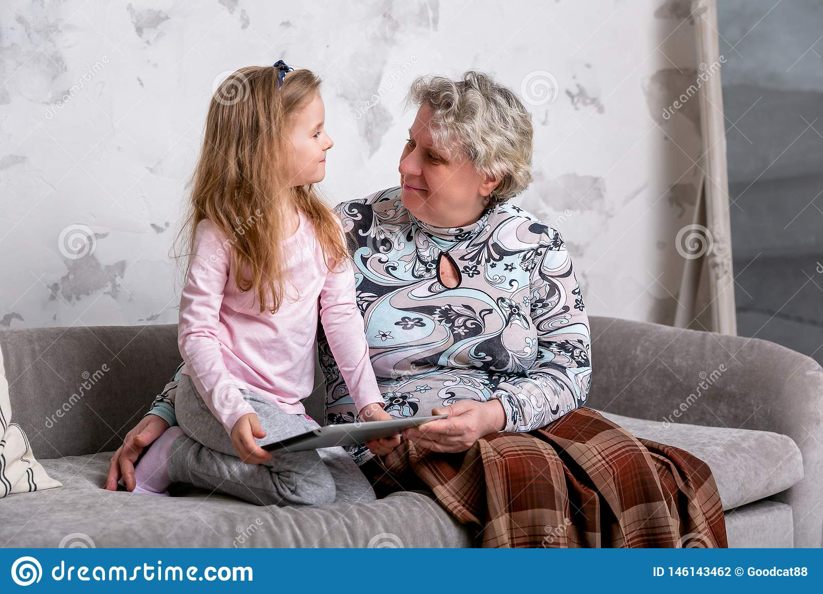 Grandmother and her little granddaughter are watching movies together and playing on the device while sitting on the sofa.