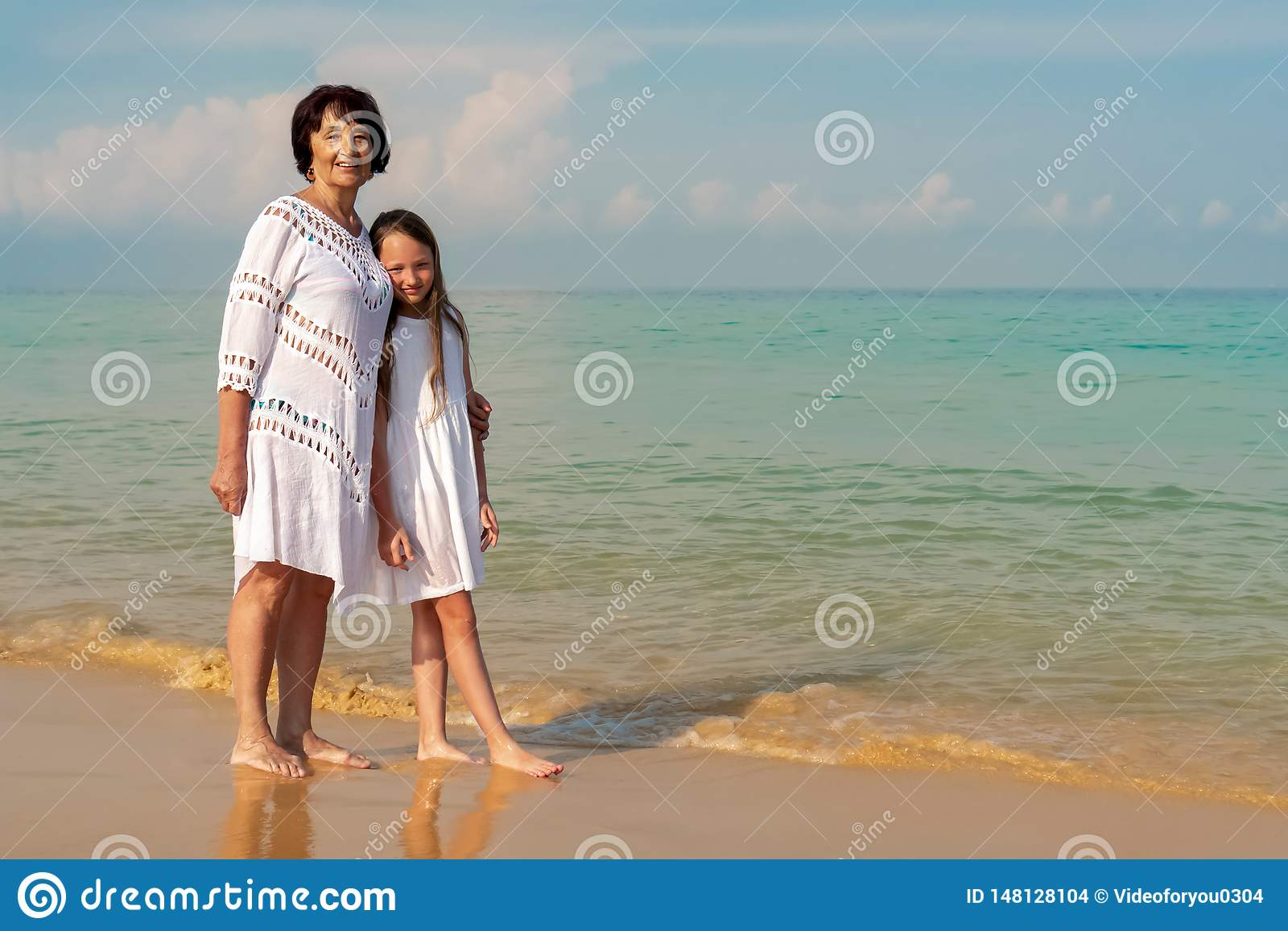 An elderly woman in a white dress with a beautiful girl in a white dress on the sea. Concept of sunny and happy summer