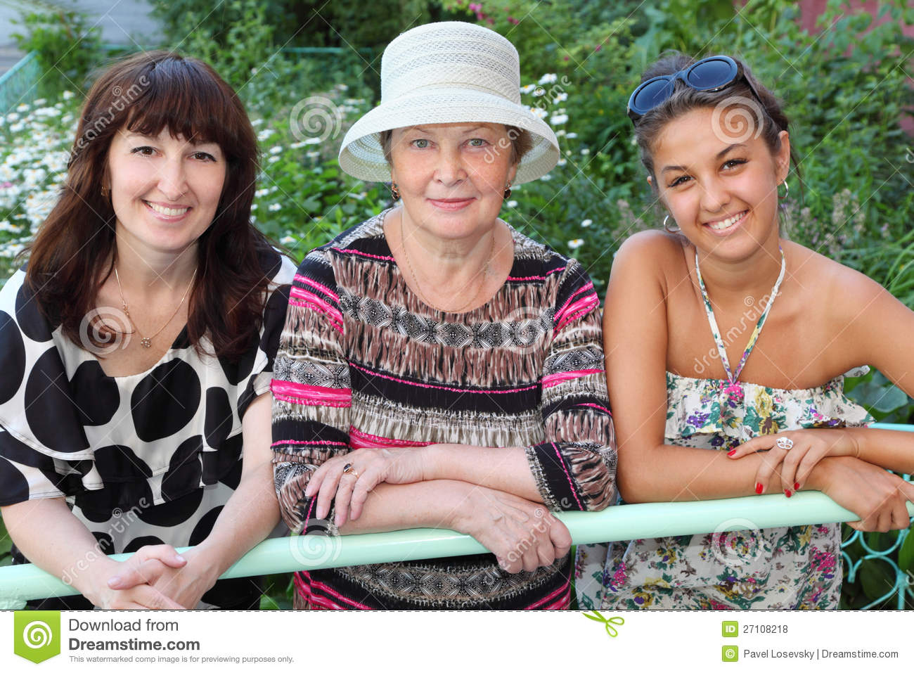 Grandmother, mother, daughter near cottage
