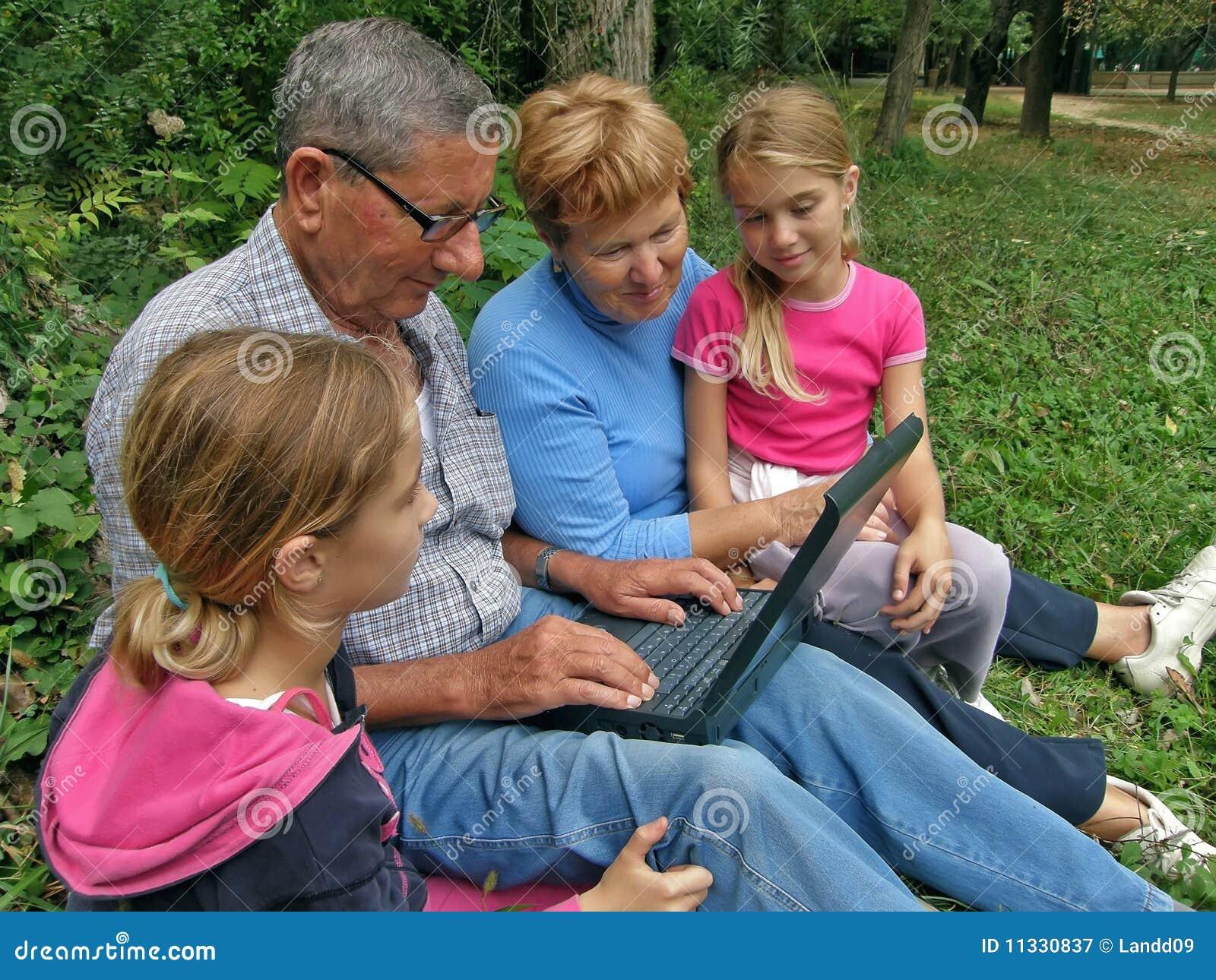 Grandparent, twins grandchild with laptop
