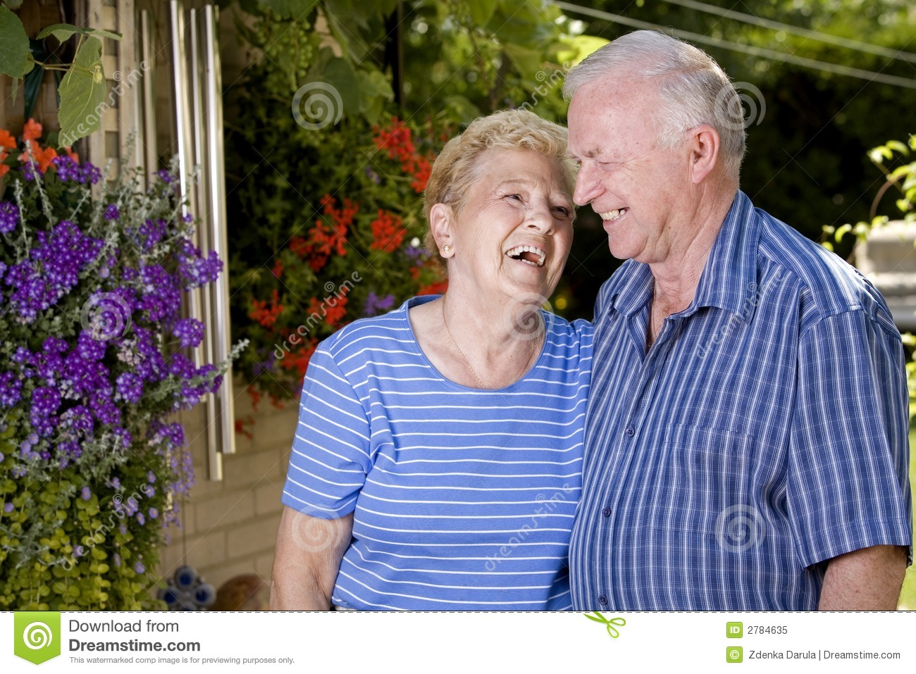 Happy grandparents in the summer looking at each other.