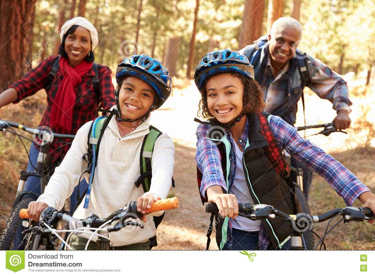Grandparents With Children Cycling Through Fall Woodland