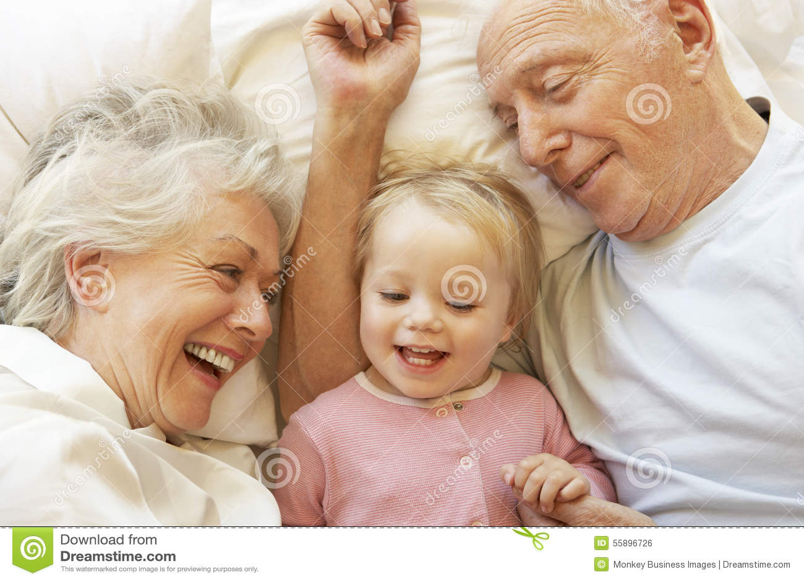 Grandparents Cuddling Granddaughter In Bed