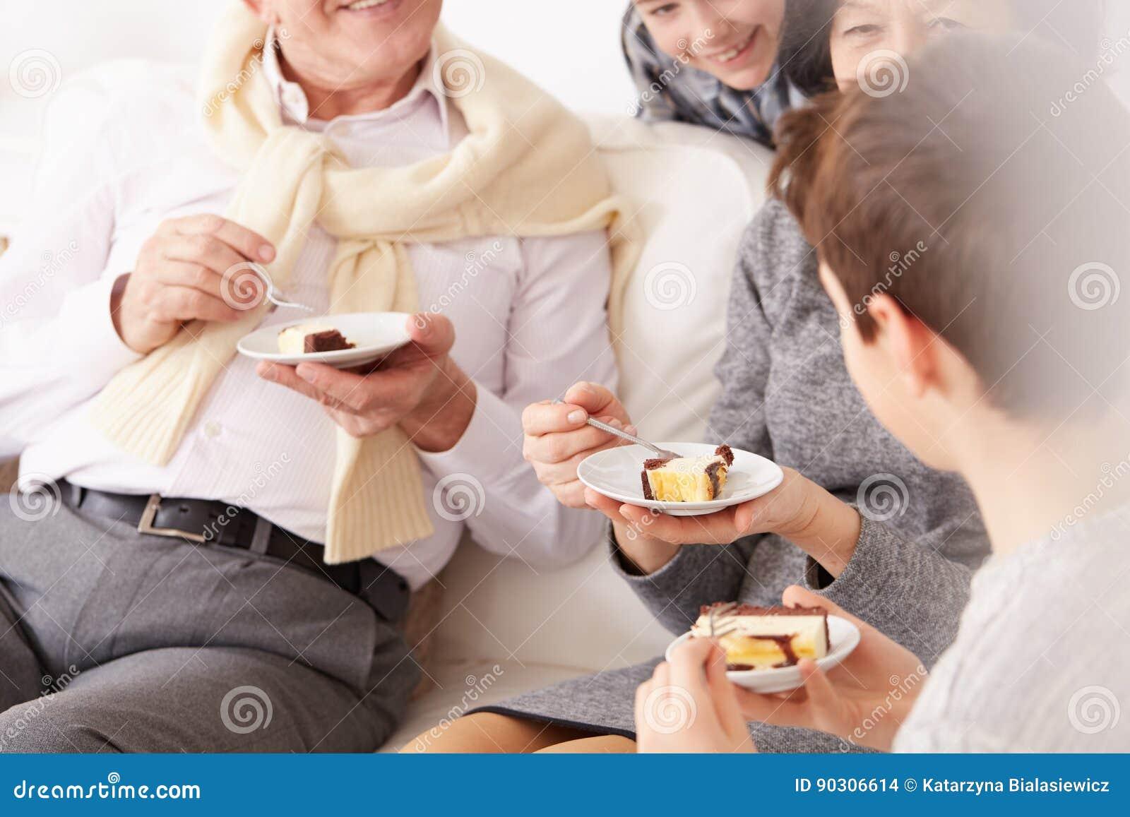 Grandparents and grandchildren eating a cake