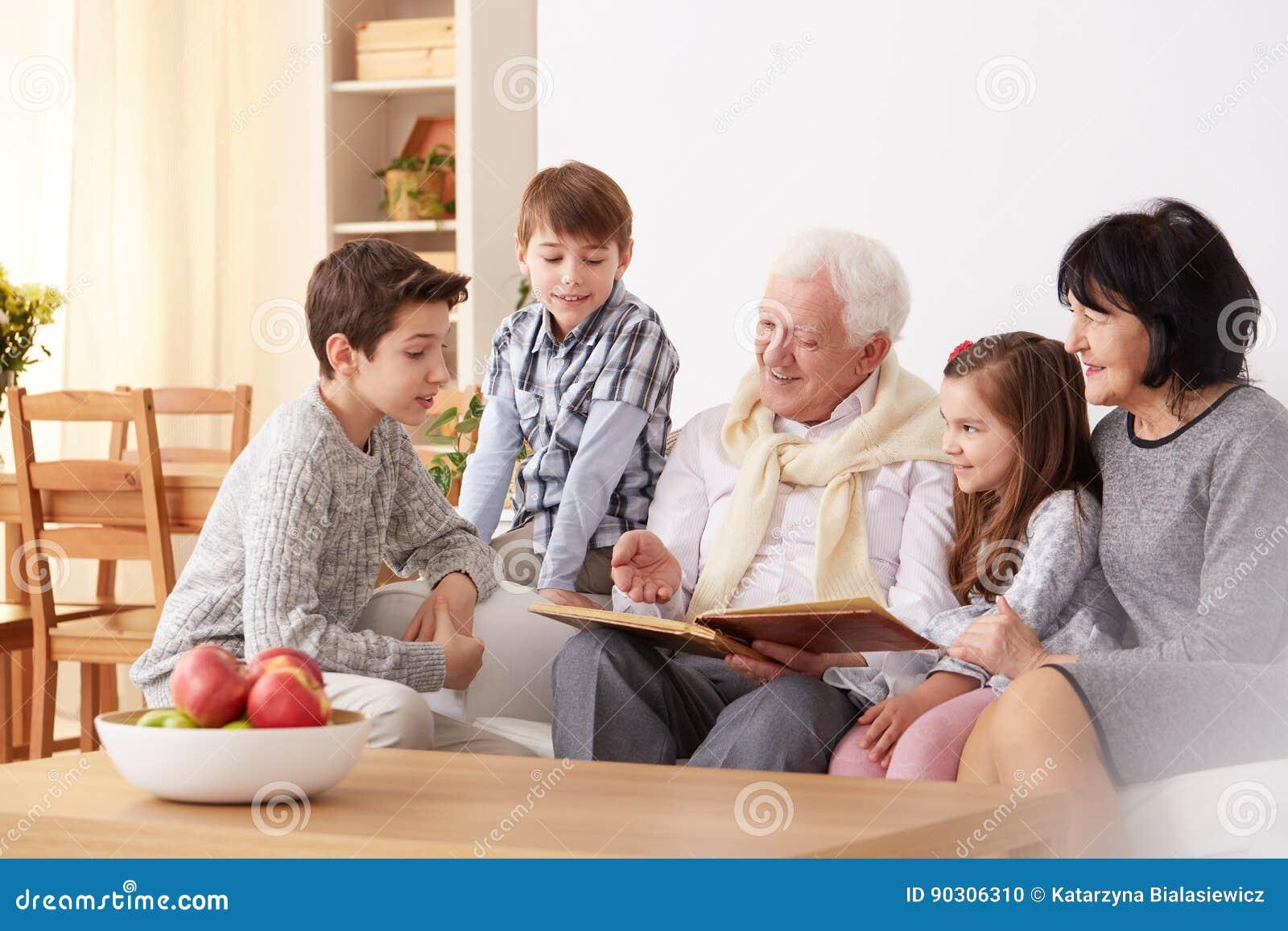 Grandparents and grandchildren with family album