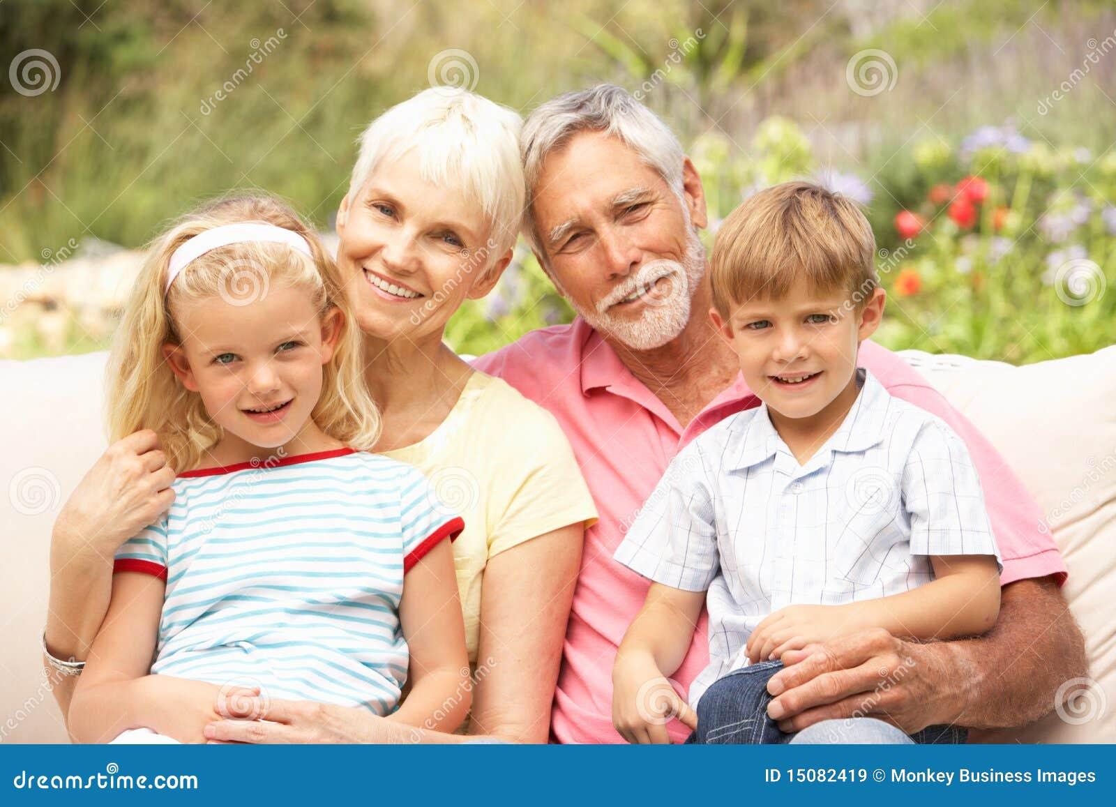 Grandparents And Grandchildren Relaxing In Garden Stock
