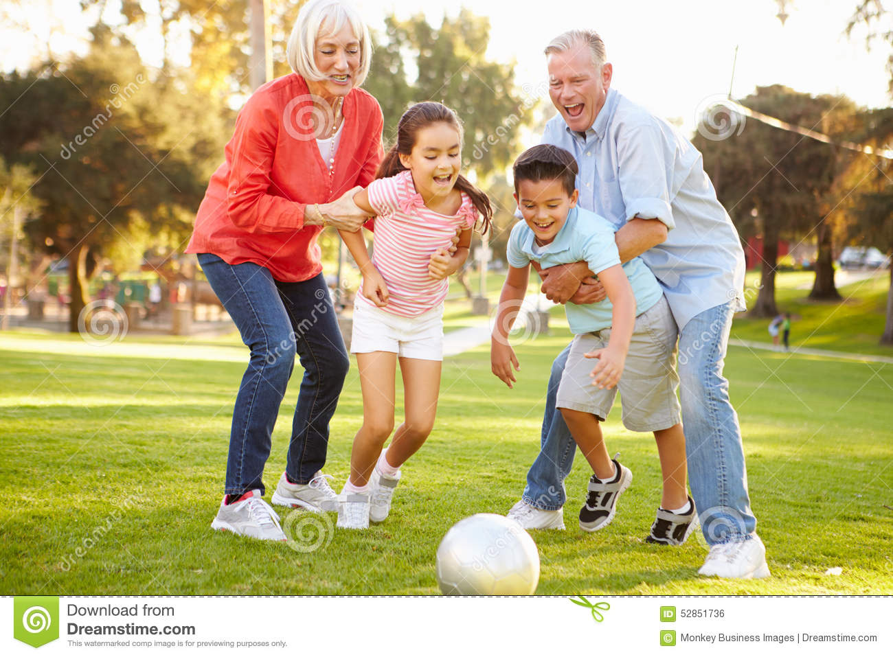 Grandparents Playing Soccer With Grandchildren In Park ...