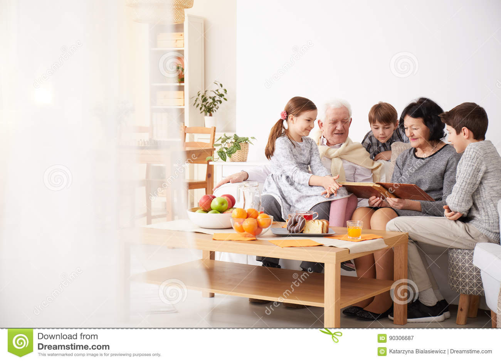 Grandparents showing photo album to their grandchildren