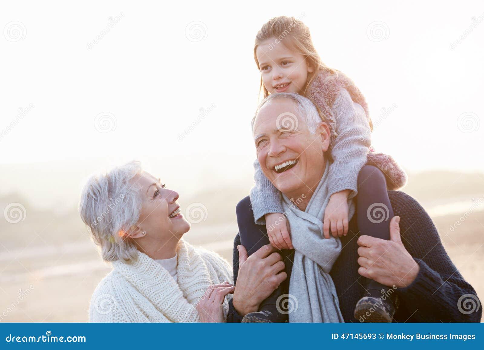Grands-parents et petite-fille marchant sur la plage d hiver