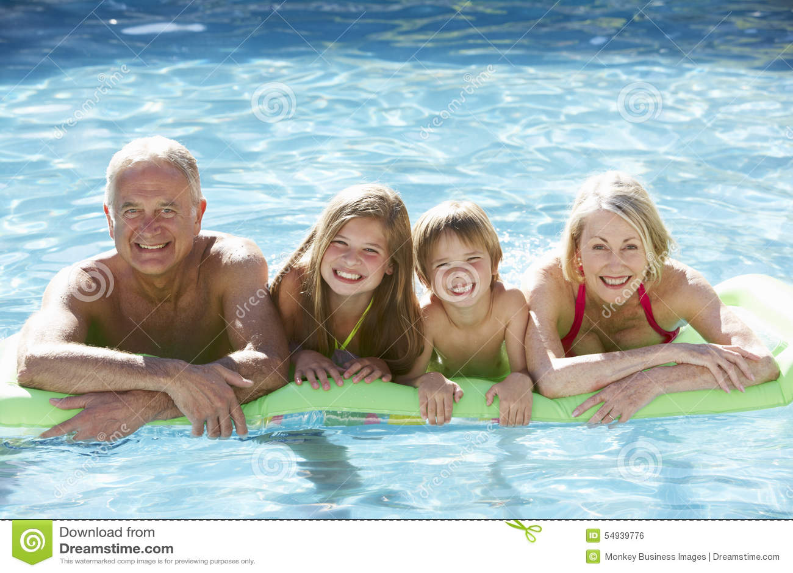 Grands-parents et petits-enfants détendant dans la piscine ensemble