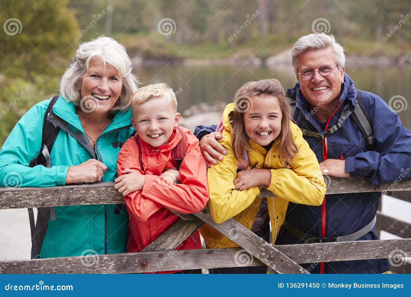 Grands-parents et petits-enfants se penchant sur une barrière en bois dans la campagne riant, secteur de lac, R-U